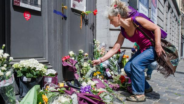 A woman lays flowers at the Jewish Museum in Brussels (AP)