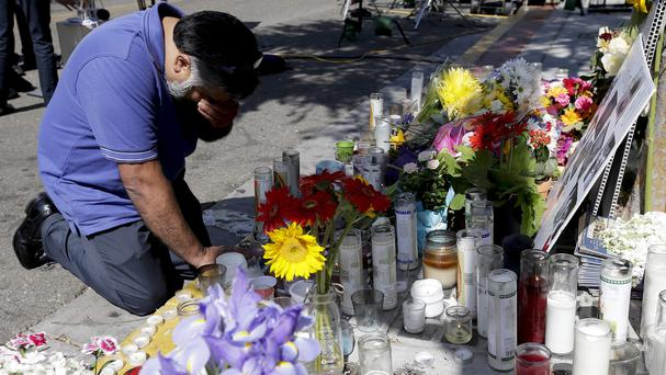 Jose Cardoso pays his respects at a makeshift memorial in front of the IV Deli Mart, where part of the mass shooting took place (AP)