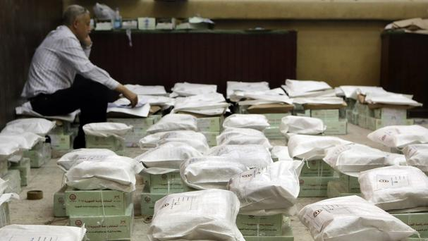 An Egyptian election worker guards boxes of ballots in Cairo (AP)