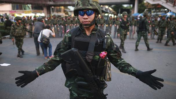 A Thai soldier gestures as he and his colleagues guard the Victory Monument during an anti-coup demonstration in Bangkok, Thailand (AP Photo/Wason Wanichakorn)