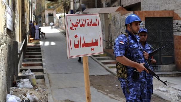 Egyptian security forces stand guard outside a polling station in Alexandria (AP)