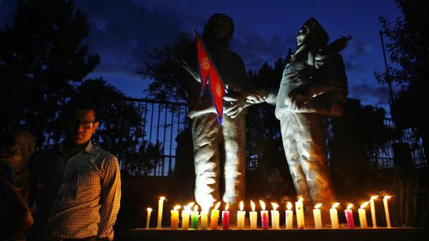 Members of the Nepal mountaineers association light candles before statues of Tenzing Norgay and Edmund Hillary (AP)