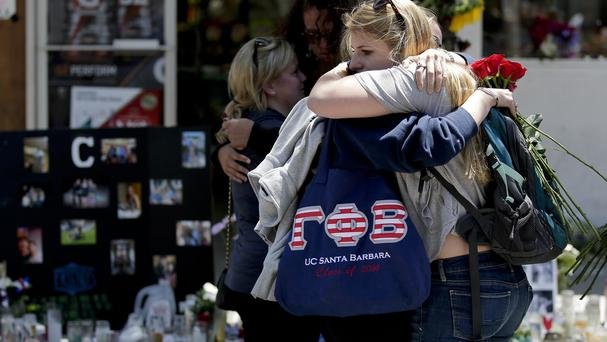 Mourners hug in front of the IV Deli Mart, where part of Friday night's mass shooting took place (AP)