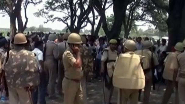 Police stand among the crowd near where two teenage sisters were found hanging from a mango tree in northern India. (AP Photo/NNIS via AP Video)