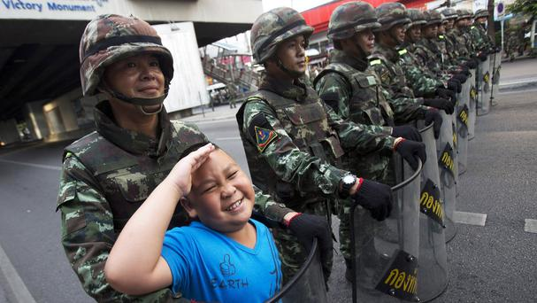 A child poses with Thai soldiers standing guard in Bangkok. (AP Photo/Sakchai Lalit)