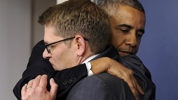 President Barack Obama gives White House press secretary Jay Carney a hug after announcing that Carney will step down later next month