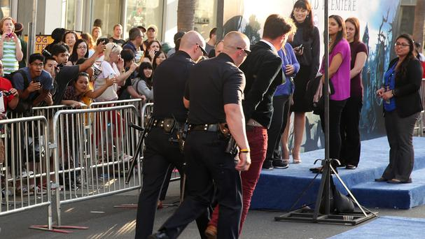 Vitalii Sediuk is taken off in handcuffs after accosting Brad Pitt at the premiere of Maleficent in Los Angeles (AP)
