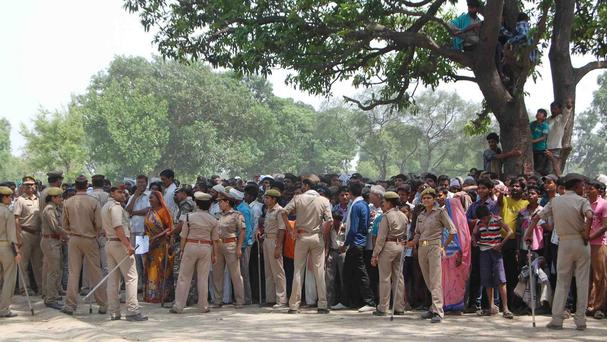 Policemen cordon off the area as villagers and others look towards the tree where two teenage girls were found hanging after they were gang raped
