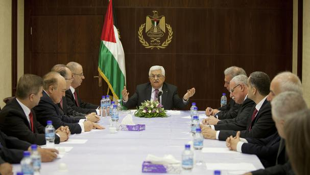 Palestinian President Mahmoud Abbas, centre, meets cabinet members of its unity government (AP)