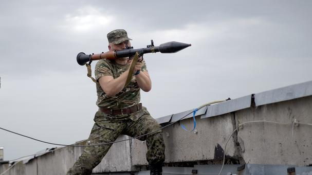 A pro-Russian rebel prepares to fire a rocket-propelled grenade during clashes as they attack a border guard base held by Ukrainian troops on the outskirts of Luhansk (AP)