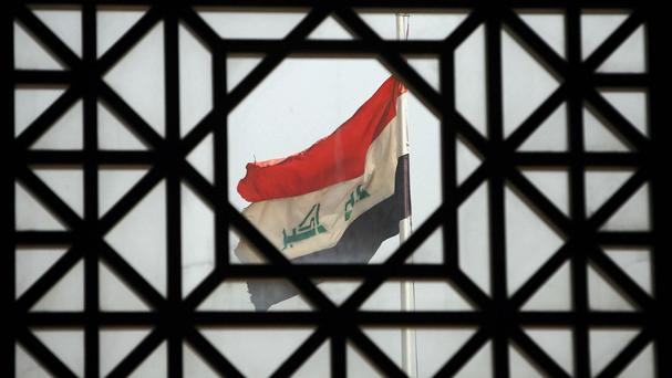 The Iraqi flag flying at Basra International Airport, Iraq, seen through a window at the airport.