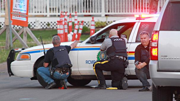 Police take cover behind their vehicles (AP/Moncton Times & Transcript, Ron Ward via The Canadian Press)