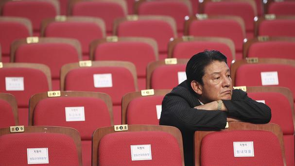An activist waits for results of South Korean polls seen as a test of public sentiment towards Park Geun-hye's handling of the ferry disaster (AP)