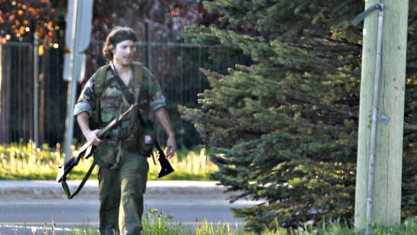 A heavily armed man that police have identified as Justin Bourque walks on Hildegard Drive in Moncton, New Brunswick