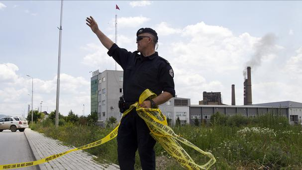 A police officer seals off the area where an explosion rocked Kosovo's main power plant (AP)