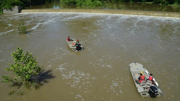Conservation officers drag the Big Blue River below the dam in the hunt for a missing teenager (AP)