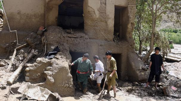 Afghans look for belongings in their house damaged after flooding in the northeastern Baghlan province (AP)