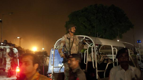 Pakistani security troops rush to Karachi airport terminal following attacks by gunmen (AP)