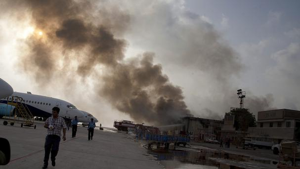 Smoke rises above the Jinnah International Airport where security forces continue to battle militants in Karachi, Pakistan (AP)