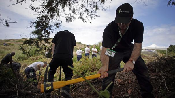 British police and forensics officers clear and dig the ground inside a cordoned-off area, in Praia da Luz, Portugal