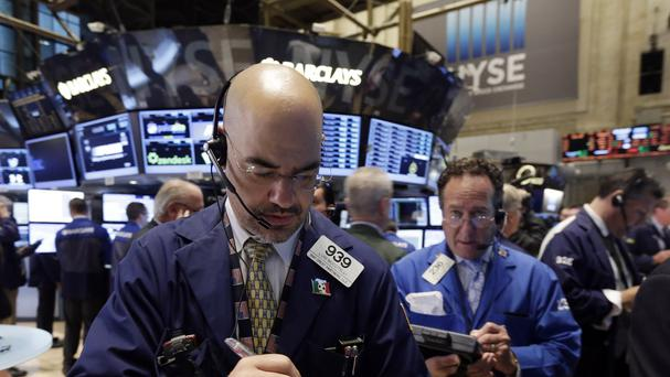 Trader Luigi Muccitelli, left, works on the floor of the New York Stock Exchange (AP)