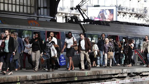 Commuters walk on a platform at the Gare St Lazare station in Paris as French rail workers strike to protest against plans to open the railways to competition. (AP Photo/Thibault Camus)