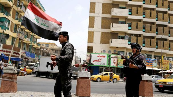 Iraqi federal policemen stand guard at a checkpoint in Baghdad (AP Photo/ Karim Kadim)