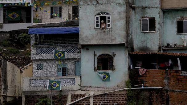 A woman stands at a window of a house near the Arena Ponte Nova stadium in Salvador (AP)