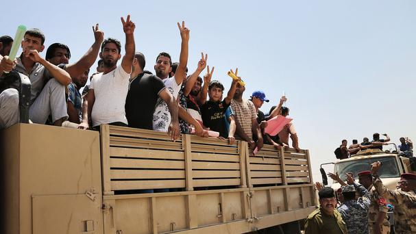 Iraqi men flash victory signs as they leave the main recruiting centre to join the Iraqi army in Baghdad. (AP)