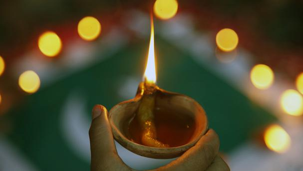 A family member lights oil lamp to pay tribute to the victims of last Sunday's attack at the Jinnah International Airport, in Karachi, Pakistan (AP)
