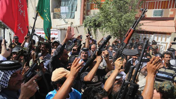 Iraqi Shia tribal fighters raise their weapons and chant slogans against the al-Qaida inspired Islamic State of Iraq and the Levant in Baghdad's Sadr city (AP)
