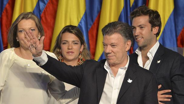 "With the word ""peace"" written on his hand, Colombian president Juan Manuel Santos waves during a victory rally next to first lady Maria Clemencia Rogriguez (AP)"