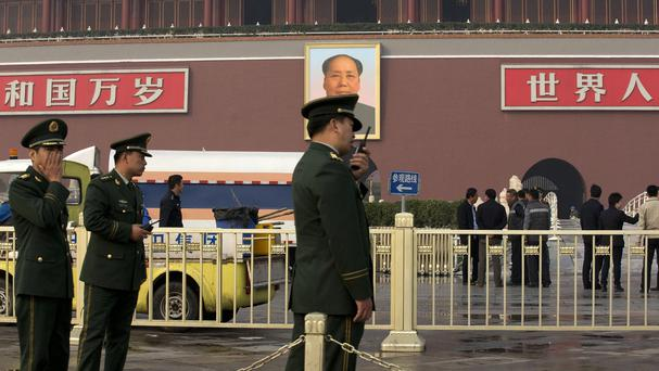 Police officers in front of Beijing's Tiananmen Gate after a car ploughed through tourists and crashed in a fireball, killing two bystanders and the three attackers (AP)