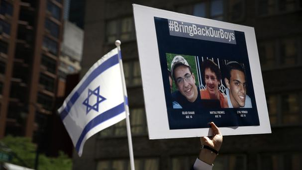 Signs and flags are displayed at a rally and prayer vigil in New York for three Israeli teenagers believed to have been abducted by Hamas in the West Bank (AP)
