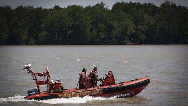 Search and rescue personnel on a speedboat search for passengers of a sunken boat on the outskirts of Banting, Malaysia (AP)