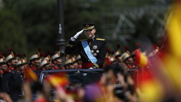 Spain's newly crowned King Felipe VI salutes to the crowd as he rides in an open-top Rolls-Royce during his arrival at the Royal Palace in Madrid