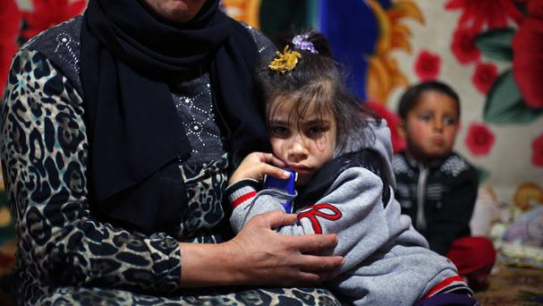 Syrian refugee Fahda, six, hangs on to her mother in the Fayda Camp in Lebanon, one of more than 50 million people who have been forced from their homes worldwide (AP)