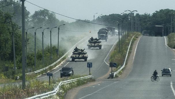 Pro-Russian troops in tanks, armoured vehicles and trucks drive towards Donetsk (AP/Evgeniy Maloletka)