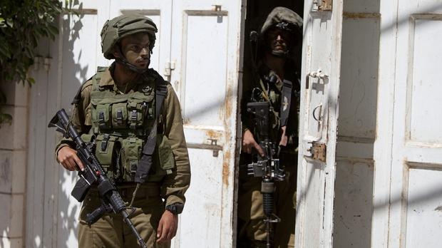Israeli soldiers search a house looking for three missing Israeli teenagers feared to have been abducted (AP Photo/Majdi Mohammed)