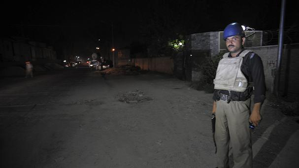 A Pakistani police officer stands guard near Peshawar airport after a gunman opened fire at a plane (AP)