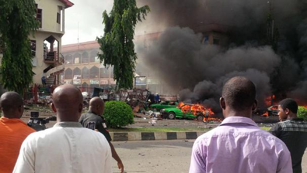 People watch as smoke fills the sky, after an explosion, at a shopping centre in Abuja, Nigeria (AP Photo)
