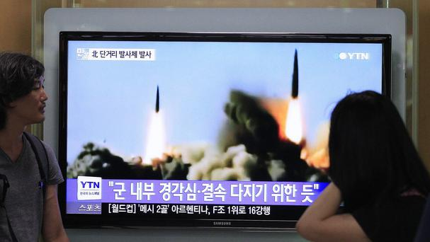 People watch a TV news programme showing the missile launch conducted by North Korea, at Seoul Railway Station in Seoul, South Korea (AP)