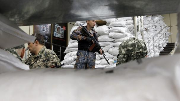 Pro-Russian fighters guard their military unit in the Ukrainian city of Donetsk (AP/Dmitry Lovetsky)