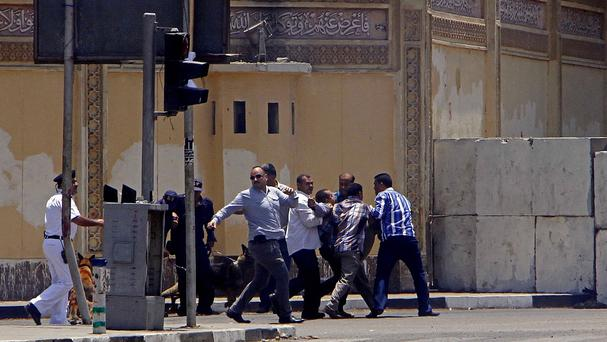 Egyptian security forces and medics help an injured man to an ambulance after bombs went off near the presidential palace in Cairo, Egypt (AP/Ahmed Abdel Fattah, El Shorouk Newspaper)