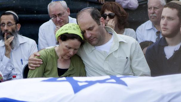 Avi and Rachel Fraenkel embrace during the funeral of their 16-year-old son Naftali (AP)
