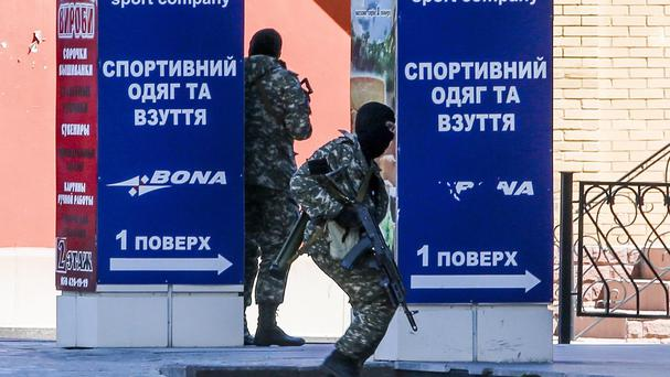 Pro-Russian fighters guard their positions during fighting near a regional police department in Donetsk, eastern Ukraine (AP)