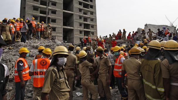 Rescuers search for workers believed buried in the rubble of a building that collapsed during monsoon rains in the outskirts of Chennai (AP)