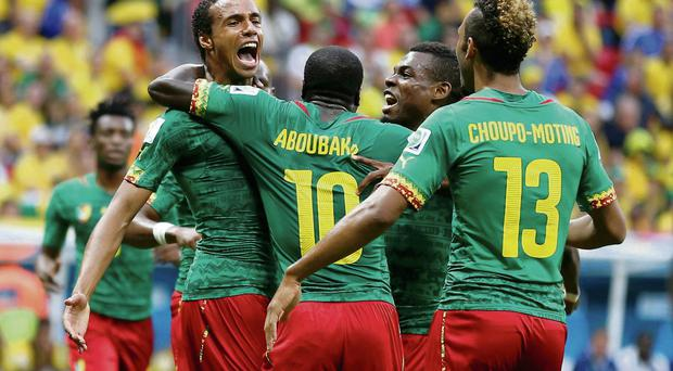 Cameroon's Joel Matip (L) celebrates his goal against Brazil with his teammates
