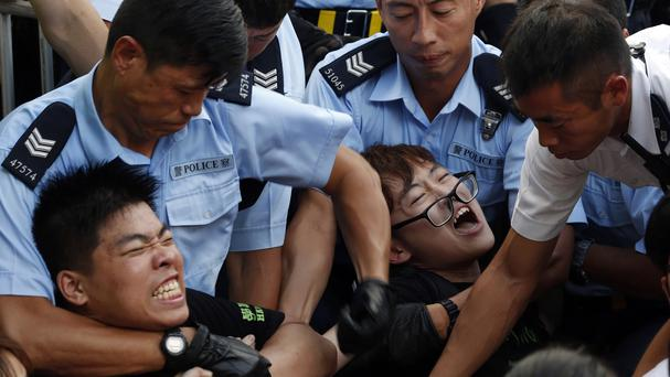 Protesters are taken away by police officers after hundreds of staged a sit-in on a street in the financial district in Hong Kong (AP)