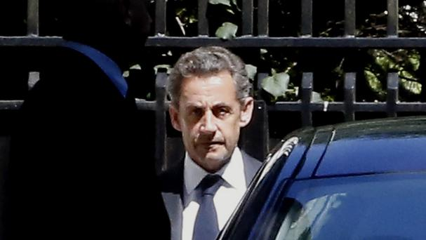 Former French President Nicolas Sarkozy leaves his house in Paris (AP)